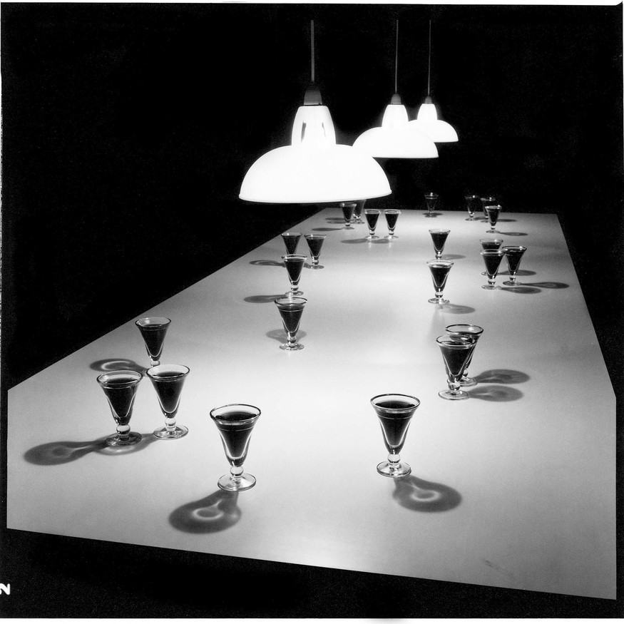 Bill Culbert Small Glass Pouring Light 1983. Serpentine Gallery, London, 1983. 25 verres bistrot, wine, Formica table, lampshades. Collection FNAC, Château d'Oiron. Photo: Bill Culbert. Reproduced courtesy Auckland University Press and the Estate of Bill and Pip Culbert