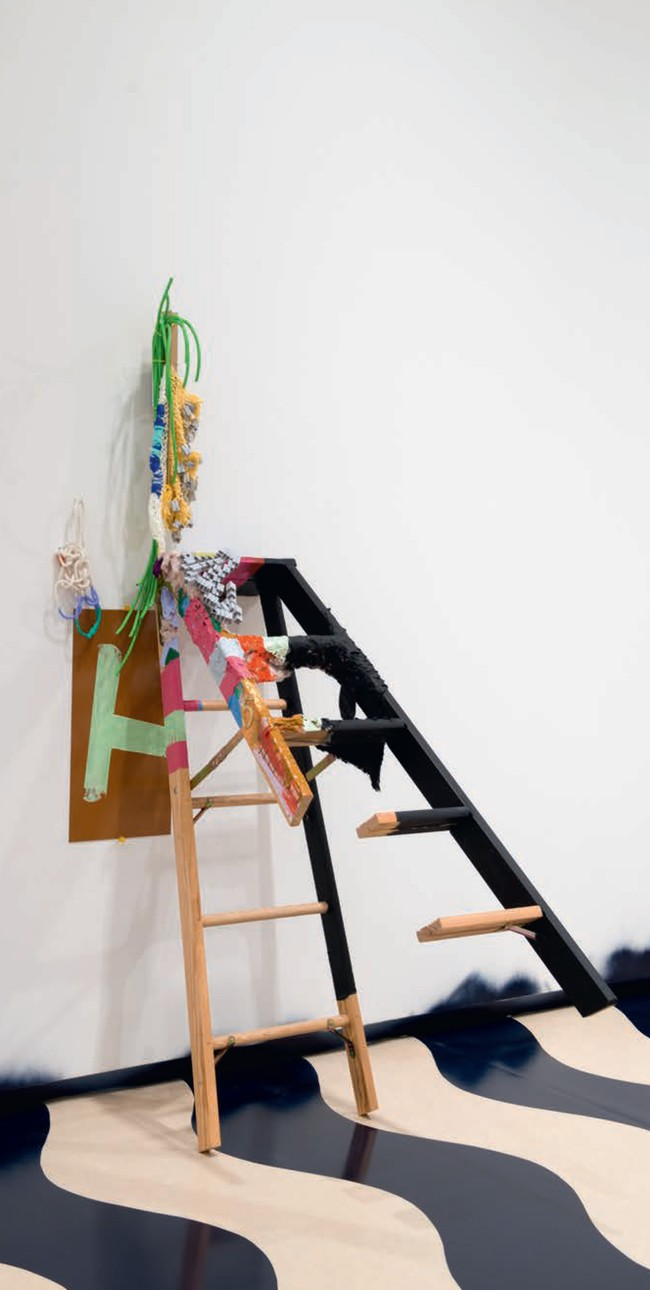 Jessica Stockholder A – H 2013. Ladder, number 5 brass, grey plastic toy modules, yard, string, green electrical cord, ochre Plexiglas, rope, acrylic paint, fake fur, cardboard angle, cable ties, TV mount, white hook, yellow tacks, 2146 x 686 x 1245 mm, installation view, A world undone, Auckland Art Gallery Toi o Tāmaki, November 2014–April 2015